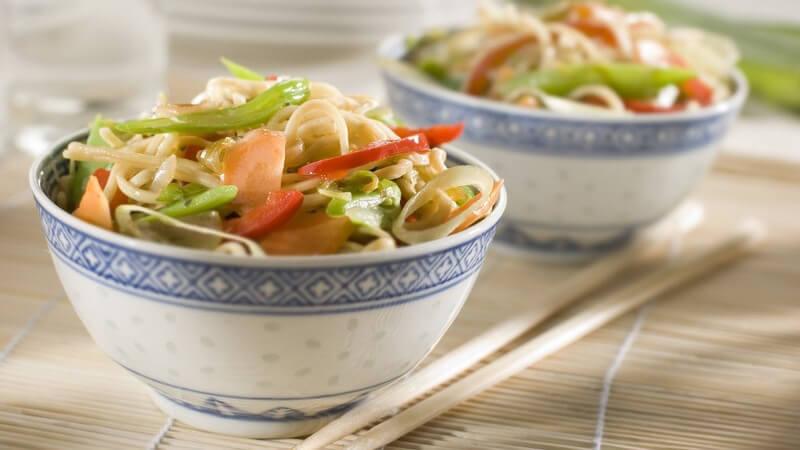 Die asiatische Küche ist auch hierzulande sehr beliebt - wers richtig machen will, probiert sich im Essen mit Ess-Stäbchen