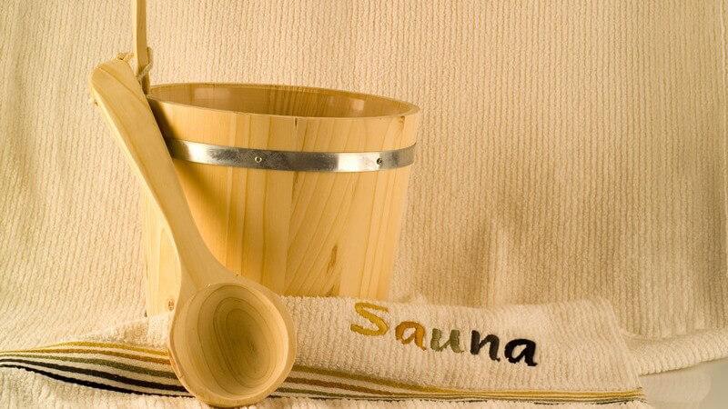 Zu den wichtigsten Saunautensilien zählen der Ofen, die Steine, Aufgusszubehör und die Saunabürste