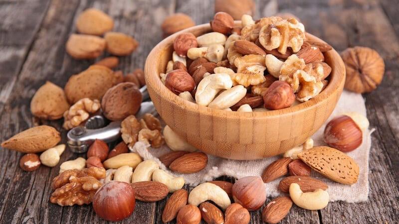 Wer Studentenfutter selbst mischen möchte, benötigt verschiedene Nusssorten wie z.B. Cashewkerne, Haselnüsse und Walnüsse sowie trockenes Obst wie Rosinen oder Aprikosen