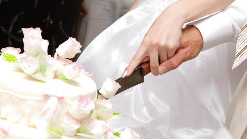 In den meisten Fällen entscheidet sich das Hochzeitspaar für eine mehrstöckige Torte - auch das gemeinsame Anschneiden gehört zur Tradition