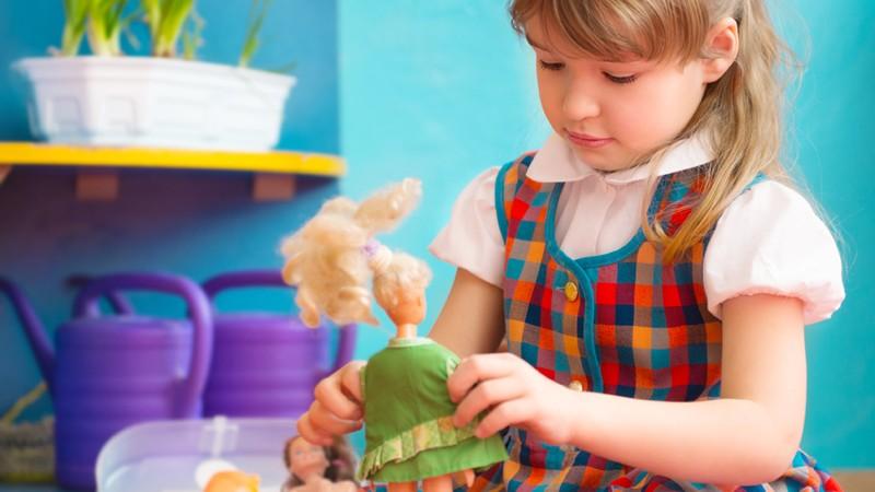 Mädchen spielt mit Puppen