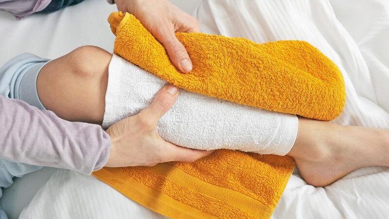 Die Durchführung von Wadenwickeln zum Senken von hohem Fieber