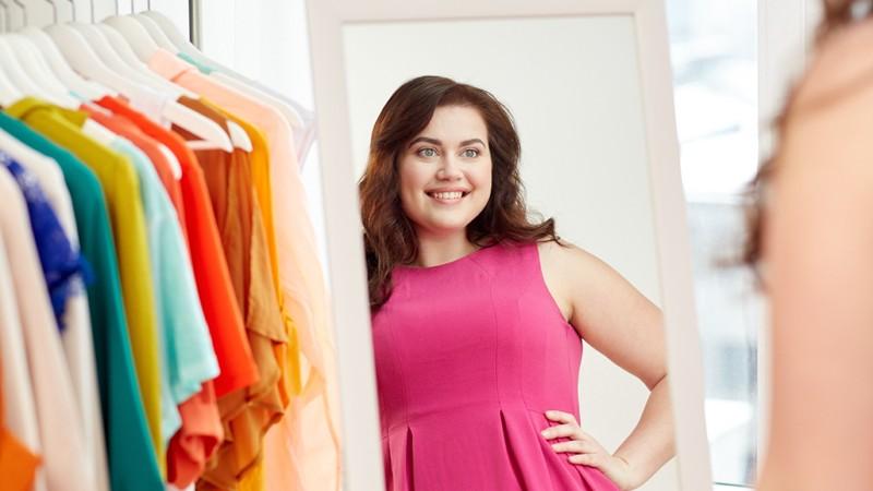 Frau mit Übergewicht posiert vor einem Spiegel